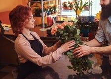 Mazzo d'acquisto maschio barbuto dei fiori al negozio floreale Fotografie Stock