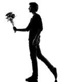 Mazzo d'offerta dei fiori della siluetta del giovane Fotografie Stock Libere da Diritti
