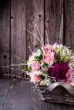Mazzo dai gillyflowers e dal alstroemeria nel canestro su vecchio Fotografia Stock Libera da Diritti
