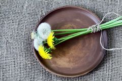 Mazzo dei denti di leone legati con cordicella sul piatto rotondo di marrone dell'argilla Tela homespun approssimativa, tela da i fotografie stock