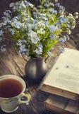 Mazzo dei fiori blu di estate, della tazza di tè e dei libri dell'annata fotografia stock