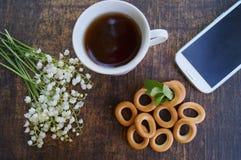 Mazzo dei fiori e della tazza di tè su una tavola di legno con il telefono con uno schermo in bianco Fotografie Stock Libere da Diritti