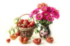 Mazzo dei fiori e dei pomodori rossi su un fondo bianco fotografie stock libere da diritti