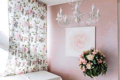 Mazzo dei fiori gialli e rosa contro lo sfondo dell'immagine di una rosa su una parete rosa fotografia stock