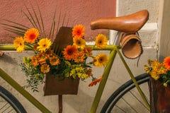Mazzo dei fiori gialli ed arancio sulla bicicletta Fotografie Stock