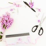 Mazzo dei fiori porpora, dei nastri miseri, delle clip, della penna, delle forbici e del taccuino su fondo bianco Disposizione pi Immagini Stock