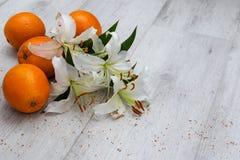 Mazzo dei gigli bianchi sul pavimento con le arance fotografie stock