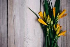 mazzo dei gigli gialli su un fondo di legno, mazzo di nozze fotografia stock