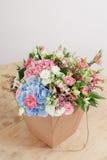 Mazzo dei ricchi dell'ortensia Fondo floristico d'annata, rose variopinte, nell'elaborazione del pacchetto sulla tavola di legno Fotografie Stock Libere da Diritti