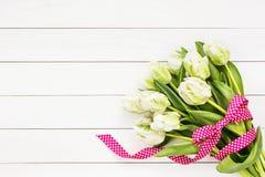 Mazzo dei tulipani bianchi decorati con il nastro su fondo di legno bianco Vista superiore Fotografie Stock