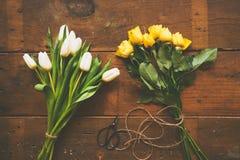 Mazzo dei tulipani bianchi e delle rose gialle su backgound di legno a Fotografie Stock Libere da Diritti