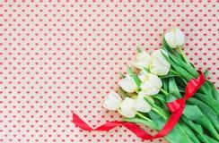 Mazzo dei tulipani bianchi sugli ambiti di provenienza dei cuori Copi lo spazio Immagine Stock