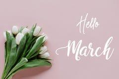 Mazzo dei tulipani bianchi sul rosa con ciao l'iscrizione di marzo Immagini Stock