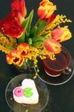 Mazzo dei tulipani e della mimosa con una tazza di tè e del dolce Fotografia Stock