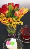 Mazzo dei tulipani e della mimosa con una tazza di tè e del dolce Immagini Stock Libere da Diritti