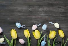 Mazzo dei tulipani gialli e delle uova di Pasqua colorate su un BAC di legno Fotografie Stock