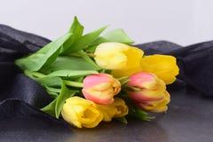 Mazzo dei tulipani multicolori su un panno grigio Piovuto appena sopra romanzesco Immagini Stock