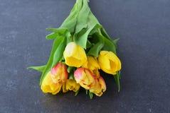 Mazzo dei tulipani multicolori su un panno grigio Piovuto appena sopra romanzesco Immagine Stock