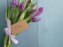 Mazzo dei tulipani porpora legati con il nastro sulla tavola di legno blu con la carta di carta per l'8 marzo Immagine Stock