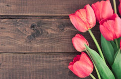 Mazzo dei tulipani rossi su un fondo di legno Piovuto appena sopra Immagine Stock Libera da Diritti