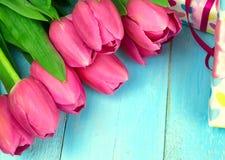Mazzo dei tulipani sulla tavola di legno blu con il contenitore di regalo Giorno felice del ` s delle donne 8 marzo , Giorno del  Immagine Stock Libera da Diritti