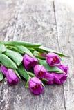 Mazzo dei tulipani viola sulla tavola di marrone della quercia Fotografia Stock