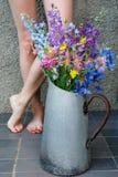 Mazzo dei wildflowers multicolori in una vecchia brocca del metallo contro lo sfondo delle gambe femminili fotografia stock libera da diritti