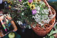 Mazzo dei Wildflowers in vaso di vetro su fondo di legno Immagine Stock
