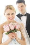 Mazzo del fiore della tenuta della sposa con lo sposo Standing In Background Immagini Stock