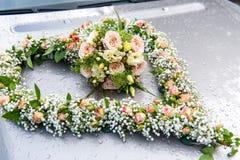 Mazzo del fiore di nozze nella forma del focolare sul cofano dell'automobile fotografia stock