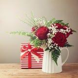 Mazzo del fiore di Rosa e contenitore di regalo sulla tavola di legno Fotografia Stock Libera da Diritti