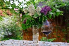 Mazzo del lill? in un vaso di vetro ed in un vetro di vino rosso fotografia stock libera da diritti