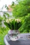 Mazzo del mughetto in un vaso su una tavola del giardino contro il fondo verde del giardino immagine stock