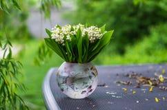 Mazzo del mughetto in un vaso su una tavola del giardino contro il fondo verde del giardino fotografia stock libera da diritti
