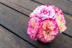 Mazzo del rosa e delle rose gialle in un vaso che si siede sul pavimento di legno marrone della plancia immagine stock libera da diritti