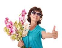 Mazzo della holding della donna di fiori maggiore. Fotografia Stock