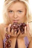 Mazzo della holding della donna di uva rossa Immagine Stock
