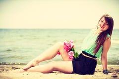 Mazzo della tenuta della donna dei fiori che si siedono sulla spiaggia Fotografia Stock Libera da Diritti