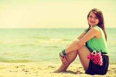 Mazzo della tenuta della donna dei fiori che si siedono sulla spiaggia Fotografia Stock