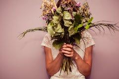 Mazzo della tenuta della giovane donna dei fiori morti Fotografia Stock