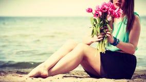 Mazzo della tenuta della donna dei fiori che si siedono sulla spiaggia Immagine Stock