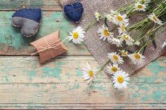 Mazzo delle margherite con i cuori del contenitore e del denim di regalo su vecchio di legno Immagine Stock Libera da Diritti