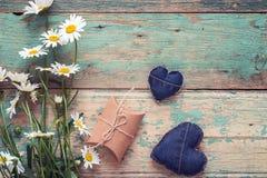 Mazzo delle margherite con i cuori del contenitore e del denim di regalo su vecchio di legno Fotografia Stock