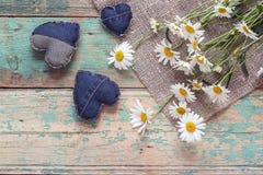 Mazzo delle margherite con i cuori del denim su vecchio fondo di legno P Fotografie Stock Libere da Diritti