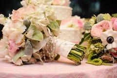 Mazzo delle rose avvolto in nastro davanti alla torta nunziale. Immagine Stock Libera da Diritti