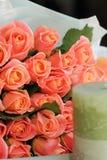 Mazzo delle rose di corallo e della candela verde oliva sulla tavola Fotografie Stock