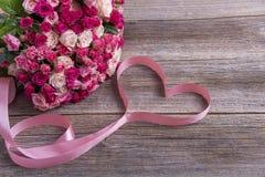 Mazzo delle rose e del cuore sui bordi di legno Fotografia Stock