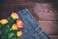 Mazzo delle rose gialle fresche che si trovano sulle blue jeans Fotografia Stock