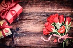 Mazzo delle rose rosse con i cuori ed i presente decorativi St Val Fotografia Stock