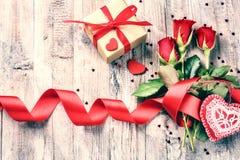 Mazzo delle rose rosse con i cuori ed i presente decorativi St Val Fotografie Stock